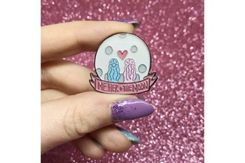 moon shaped enamel pin with two figures viewed from the back and the words me her and the moon